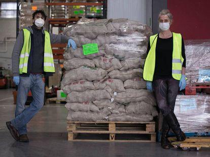 Dos colaboradores de los Bancos de Alimentos en un almacén con comida empaquetada para ser repartida.