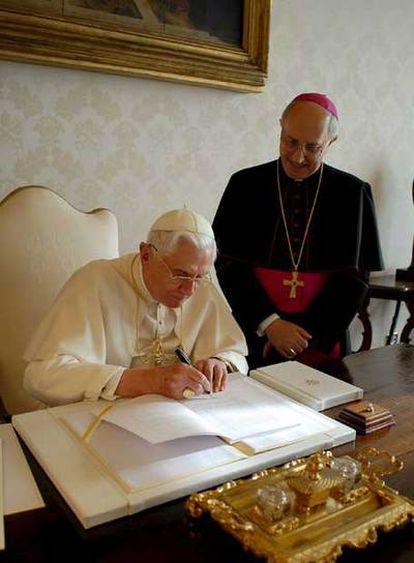 El Papa firma la encíclica<i> Spe salvi </i>ante el arzobispo Fernando Filloni.