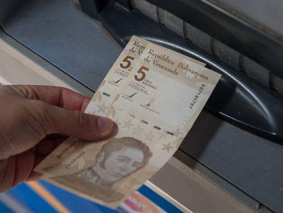 Una persona saca dos billetes de 5 bolívares digitales, la nueva divisa venezolana, este viernes en Caracas.
