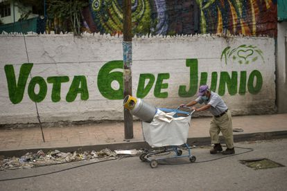 A man pushes a cart in front of a sign inviting to vote in Ecatepec, State of Mexico, on June 3.