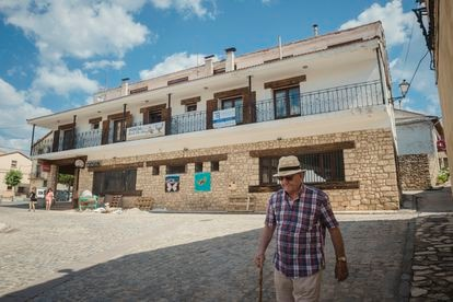 Un hombre camina frente al hostal de Griegos (Teruel) ofertado para atraer familias a la localidad.