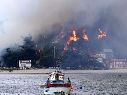 Un pesquero se aleja de la costa frente a la localidad de O Ézaro (Dumbría), en llamas por el incendio procedente de O Pindo.