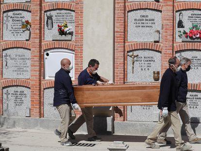 Cuatro operarios, durante el entierro de un fallecido, el pasado abril en el cementerio madrileño de la Almudena.