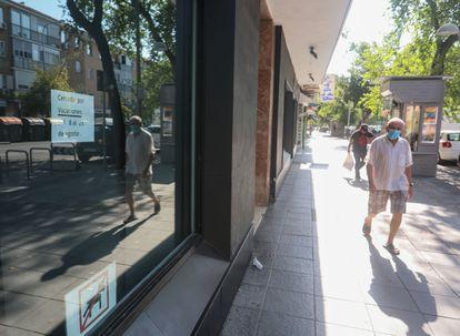 Un hombre camina por delante de un comercio cerrado en la Avenida de Oporto, distrito de Carabanchel (suroeste de Madrid) este miércoles a las 10.30.