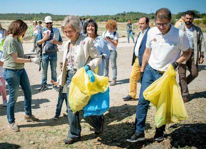 La reina Sofía (centro) recolecta residuos junto a voluntarios, este sábado, en Madrid.