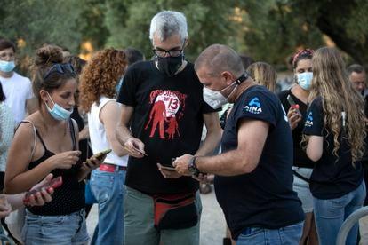 Tres personas revisan sus entradas en el festival Vida.