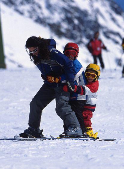 Una mujer juega con dos niños en una pista de la estación de Baqueira Beret.