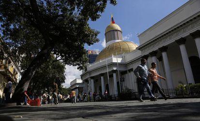 Personas caminan afuera de la Asamblea Nacional de Venezuela, en Caracas.