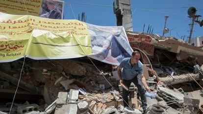 Un palestino rescata libros entre los escombros de la librería Mansur, destruida por un bombardeo israelí, en mayo en Gaza.