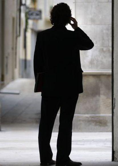 Un hombre habla por su móvil.