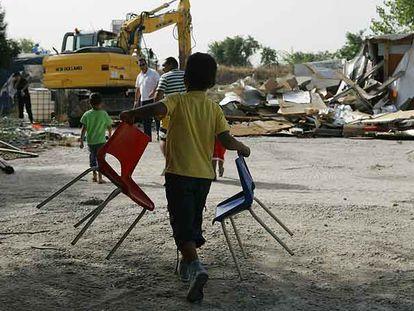 Un niño transporta dos sillas mientras una excavadora derriba una chabola en el poblado de El Salobral.