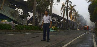 Un vigilante custodia una fábrica china que ardió en los disturbios de Binh Duong (Vietnam).