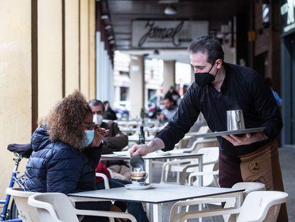 Un camarero sirve un café a una clienta en la Cafetería Tristana, durante el primer día de apertura de bares y restaurantes en Badajoz, Extremadura.