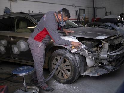 Un mecánico trabaja en un taller de chapa y pintura de vehículos de Sevilla, en febrero.