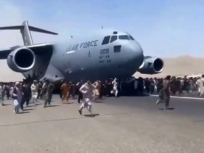 Ciudadanos afganos se agarran al fuselaje de un avión, este lunes en Kabul.