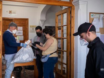El alcalde de Gines da instrucciones a uno de los voluntarios para el reparto de mascarillas.