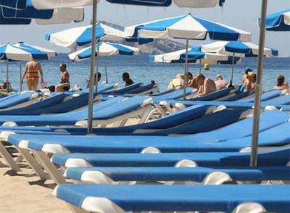 Hasta en la popular playa de Benidorm (Alicante) hay tumbonas vacías, claro síntoma del descenso del turismo de sol y playa.