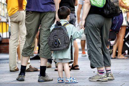 Dos mujeres llevan de la mano a un niño en el inicio de curso. Vuelta al cole en el colegio público Isabel la Católica de la calle Barceló de Madrid.