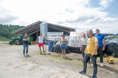 Vecinos de Serdio (Cantabria) ante unos carteles de protesta en julio.