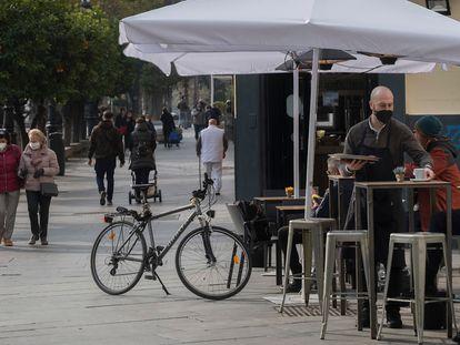 Un camarero atiende una mesa en un bar de Sevilla.