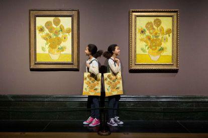 Ella (izquierda) y Eva, gemelas idénticas, posan entre las dos versiones de 'Los girasoles', de Vincent Van Gogh, expuestas en la National Gallery.