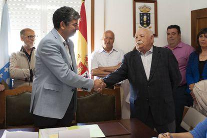 El alcalde socialista de Taboadela, Álvaro Vila (izquierda), saluda al que fue regidor durante 47 años, Manuel Gallego.