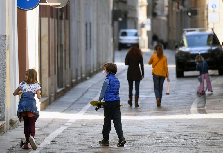 Una niña monta en patinete junto a un niño que carga un monopatín, el miércoles en Milán.