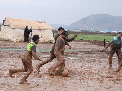 Un grupo de sirios desplazados por la ofensiva contra la provincia rebelde de Idlib (noroeste) juegan este jueves al fútbol en un campo embarrado en Sarmada.