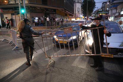 Policías israelíes instalan un puesto de control en la ciudad ultraortodoxa israelí de Bnei Brak al anochecer del martes.