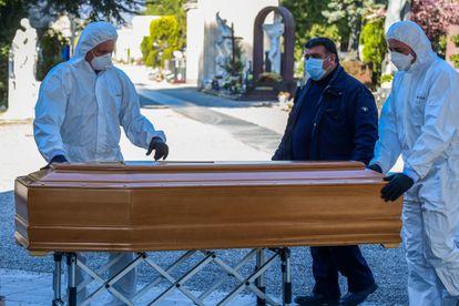 Enterradores del cementerio Monumental de Bérgamo trasladan un ataúd este lunes.