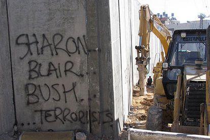 """Una pintada en la que puede leerse """"Sharon, Blair y Bush, terroristas"""", en el muro israelí."""