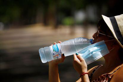 Una mujer bebe agua en Córdoba, durante la ola de calor de principio de agosto.