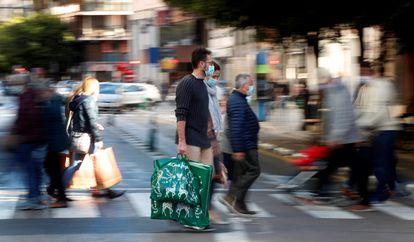 Varias personas cargan con sus bolsas tras realizar sus compras este domingo, a menos de dos semanas de celebrarse la navidad.