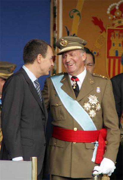 El Rey conversa con Zapatero, durante el desfile de la Fiesta Nacional.