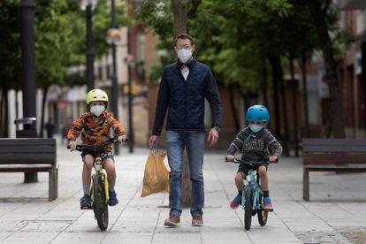 Unos niños en bicicleta pasean con su padre en Huesca con mascarillas para evitar contagios de covid-19.