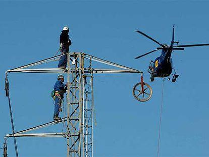 Un helicóptero colaboró en la reparación del tramo afectado por la caída de la torre por el agua del Fluvià.