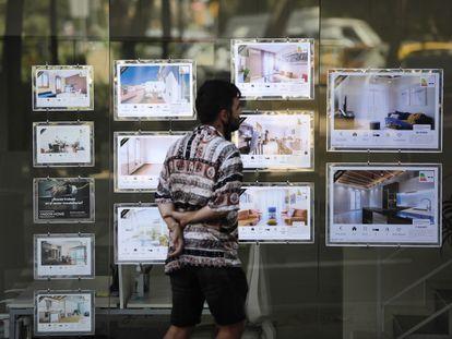 Un joven mira anuncios de alquiler de una inmobiliaria en Barcelona.