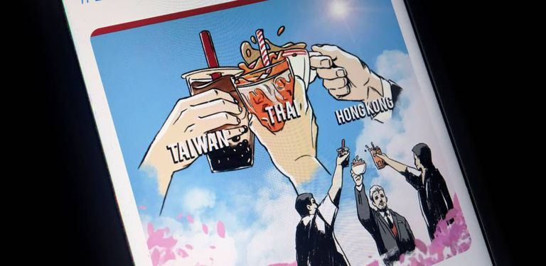 """Un móvil muestra un cartel de la """"alianza del té con leche"""" entre los internautas de Taiwán, Tailandia y Hong Kong."""