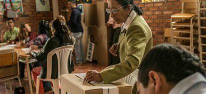 Una mujer depositando su voto.