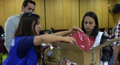 Funcionarios de la autoridad electoral abren una caja con actas de las presidenciales en Quito.