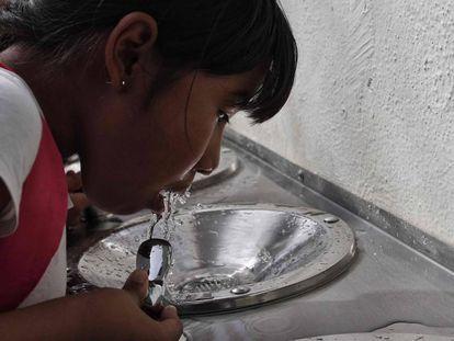 Una niña bebe agua de un bebedero en Querétaro.