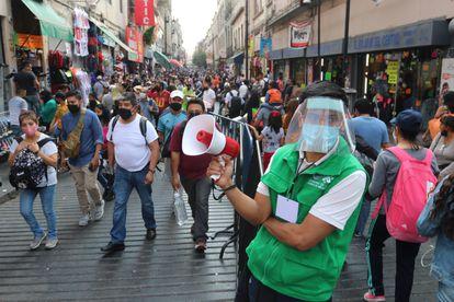 Un funcionario promueve el distanciamiento social en una concurrida calle comercial del centro histórico de la Ciudad de México.