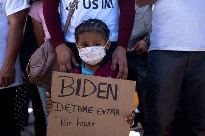Una niña hondureña sostiene un cartel en una manifestación de migrantes en Tijuana (México), este martes.