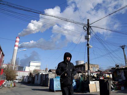Un hombre camina, en noviembre de 2019, frente a una planta de generación de electricidad a partir de carbón en Harbin (China).