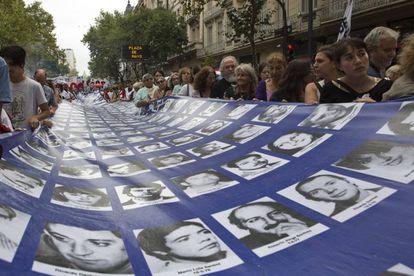 Una multitud lleva la pancarta con los nombres y rostros de los desaparecidos en la dictadura.