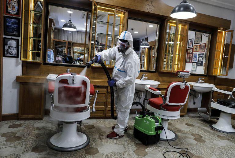 Un trabajador desinfecta una barbería en Roma este viernes.