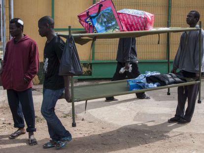 Residentes del Centro de Estancia Temporal de Inmigrantes (CETI) de Melilla trasladan unas literas, en una imagen de archivo de 2019.
