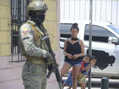 Vecinos de Guayaquil miran a uno de los militares desplegados desde este martes en las calles de la ciudad.