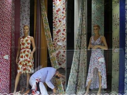 Un vendedor, trabaja en un escaparate durante el inicio de la reapertura gradual de las actividades comerciales en el centro de Ciudad de México.