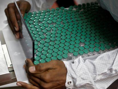 Un empleado del laboratorio Serum Institute de la India, extrae viales de la vacuna de AstraZeneca contra la covid-19.